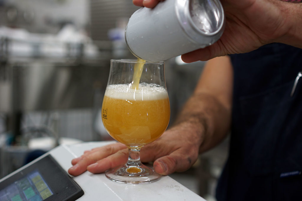 Tasting a can of beer during a packaging day at the Beerbliotek Brewery.