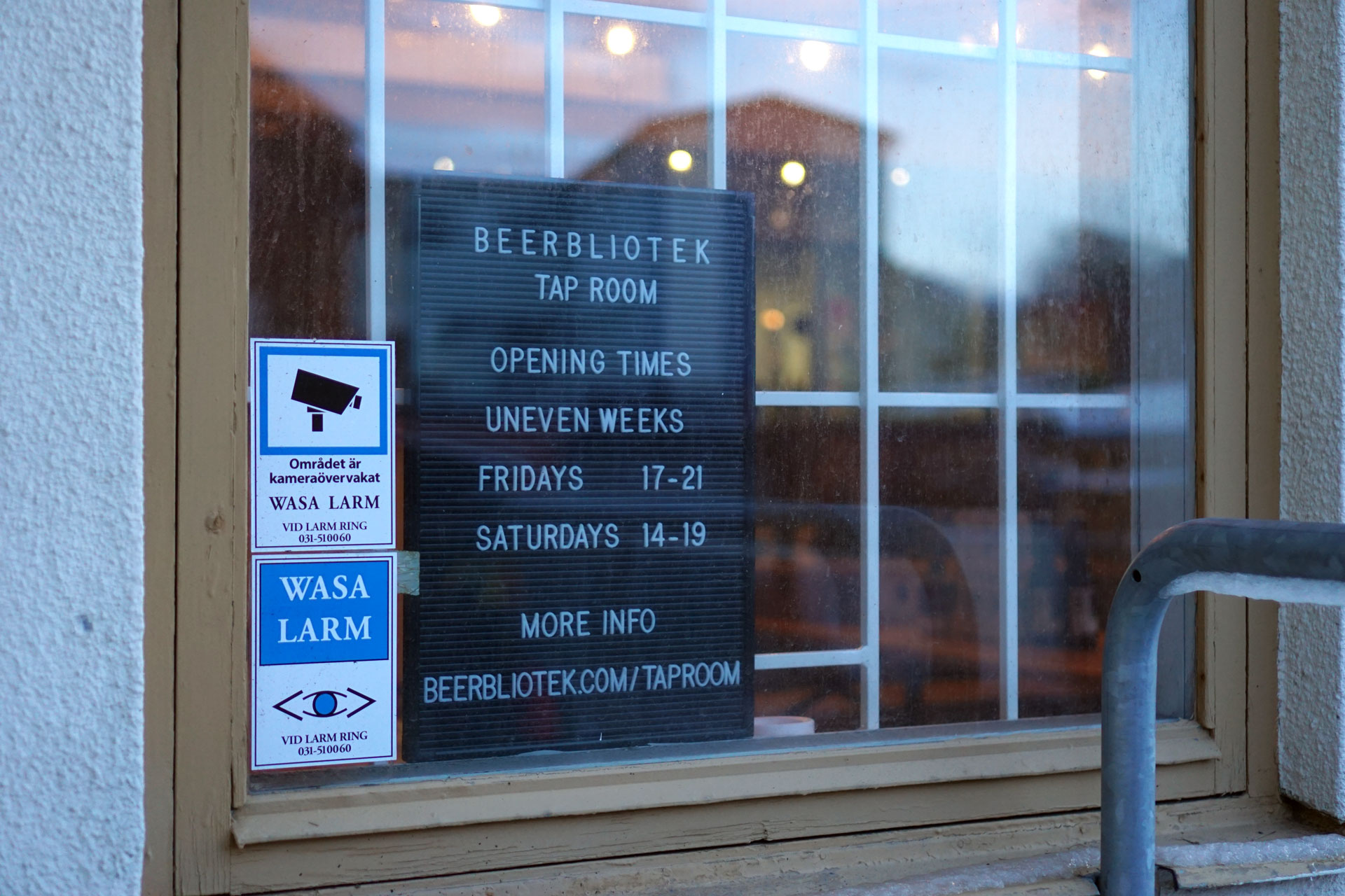A sign with the opening times in the window of the Beerbliotek Tap Room in Gothenburg Sweden.