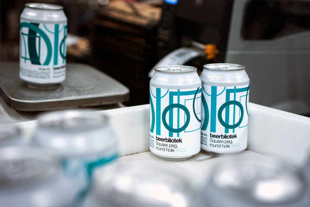 Two cans on packaging day of Square peg, round hole, a White IPA, brewed by Swedish Craft Brewery Beerbliotek.