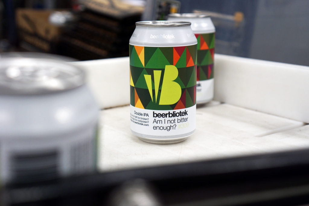 A photo of two cans on packaging day of, Am I not bitter enough? A Double IPA, brewed at Swedish Craft Brewery Beerbliotek.