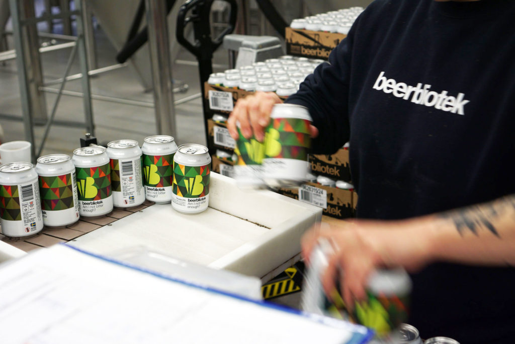 A photo of cans being labelled on packaging day of, Am I not bitter enough? A Double IPA, brewed at Swedish Craft Brewery Beerbliotek.