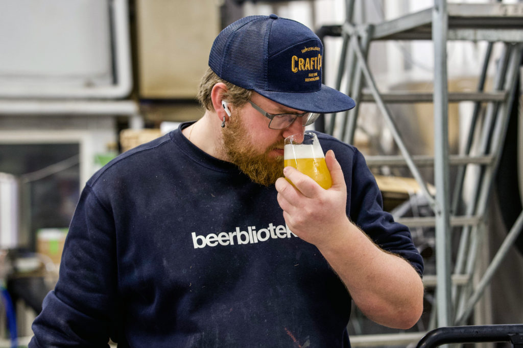 Axel tasting beer from a glass of Forward with the goat, a Belgian Pale Ale, on packaging day, brewed at Swedish Craft Brewery Beerbliotek.