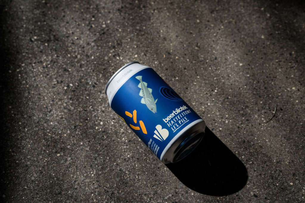 A photo of a can of Hasselssons Li'l Pils, an Unfiltered Pilsner, for brewed for Hasselssons seafood restaurant in Majorna by Swedish Craft Brewery Beerbliotek.