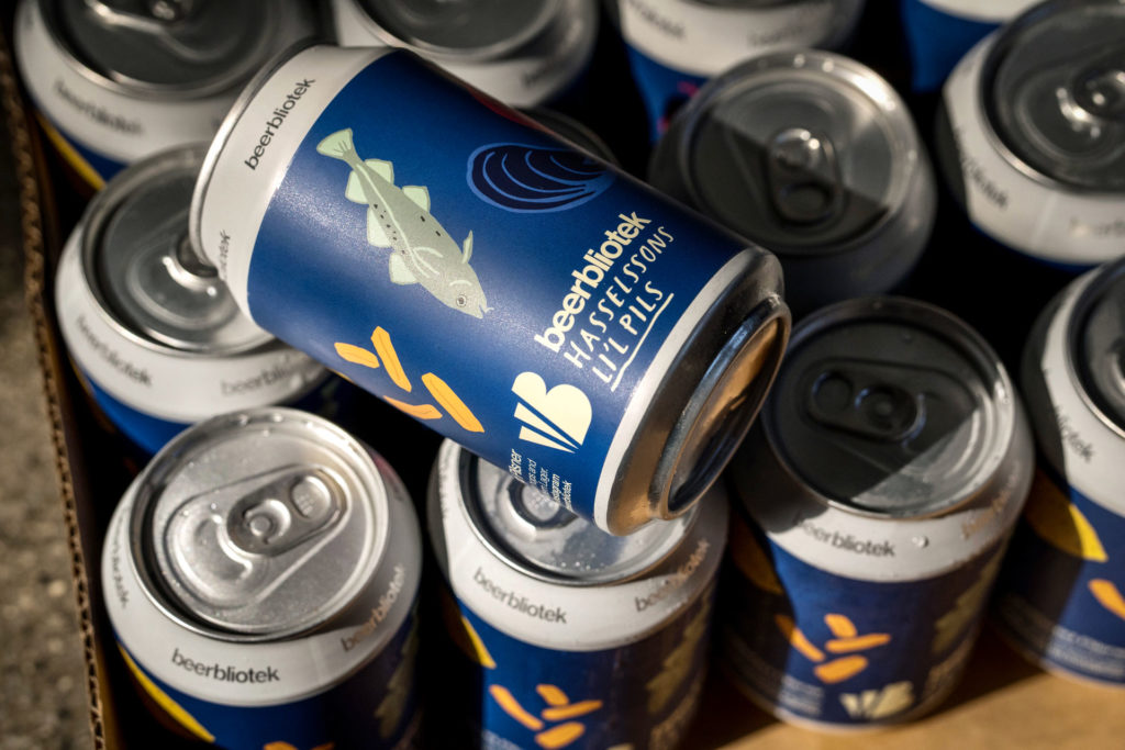 A photo of a cans of Hasselssons Li'l Pils, an Unfiltered Pilsner, for brewed for Hasselssons seafood restaurant in Majorna by Swedish Craft Brewery Beerbliotek.