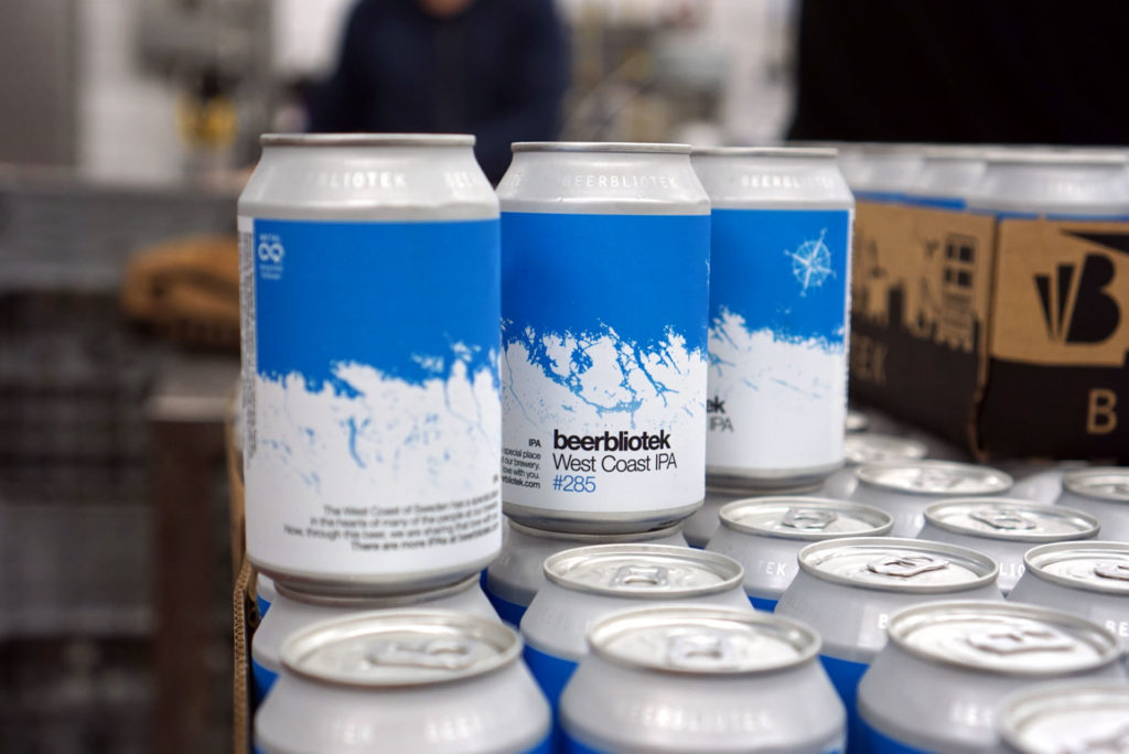 Three cans of West Coast IPA during packaging in the Swedish Brewery Beerbliotek.