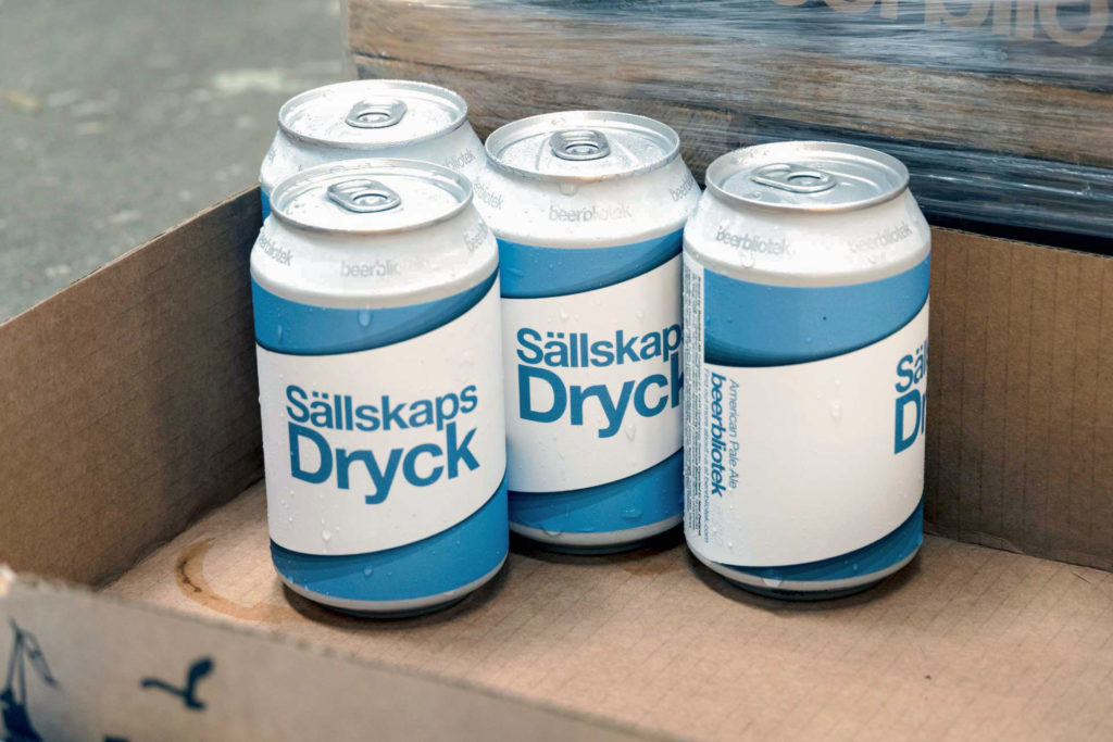 A photo of cans in a box of Sällskapsdryck - an American Pale Ale on packaging day, at Swedish Craft Brewery Beerbliotek.