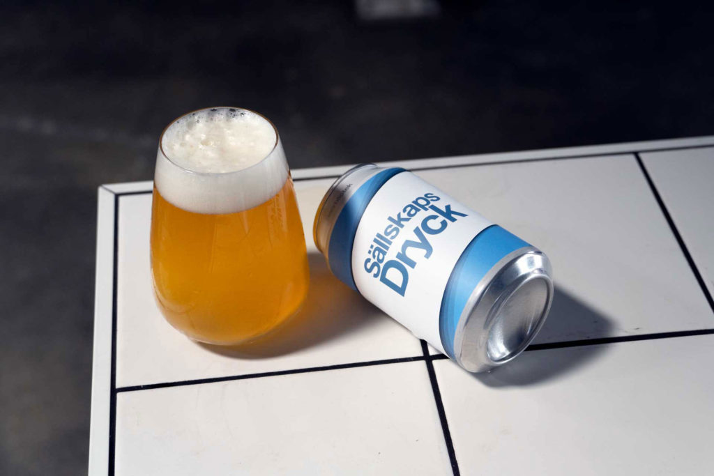 A tasting photo of beer in a glass next to the can of Sällskapsdryck, an American Pale Ale, brewed at Swedish Craft Brewery Beerbliotek.