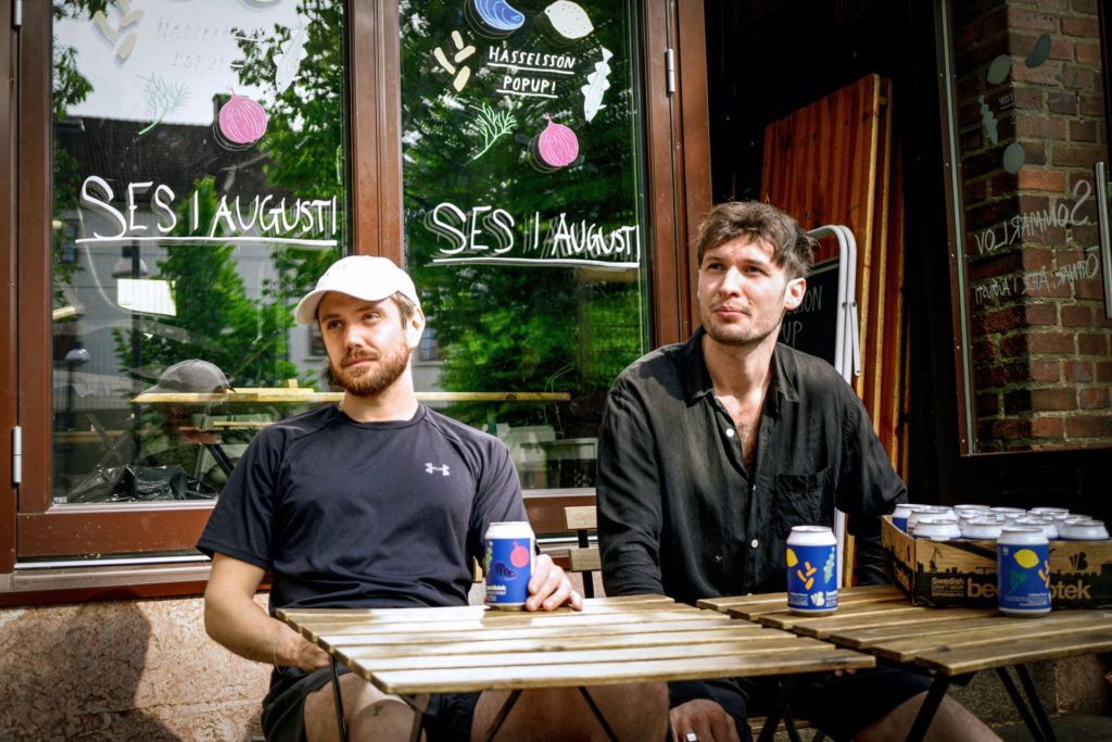 Adam Axelsson and Oliver Bull, two owners of Hasselssons - a seafood restaurant Pop Up in Majorna, Gothenburg, with their Hasselssons Li'l Pils beer brewed by Beerbliotek, a Swedish Craft Brewery from Gothenburg, Sweden.