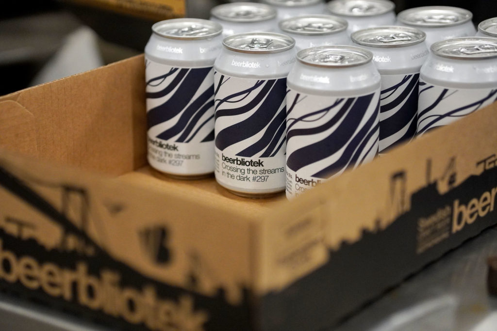 Labeled cans of Crossing the streams in the dark, a Black IPA, in a box brewed in Gothenburg, by Swedish Craft Brewery Beerbliotek, during the packaging day.