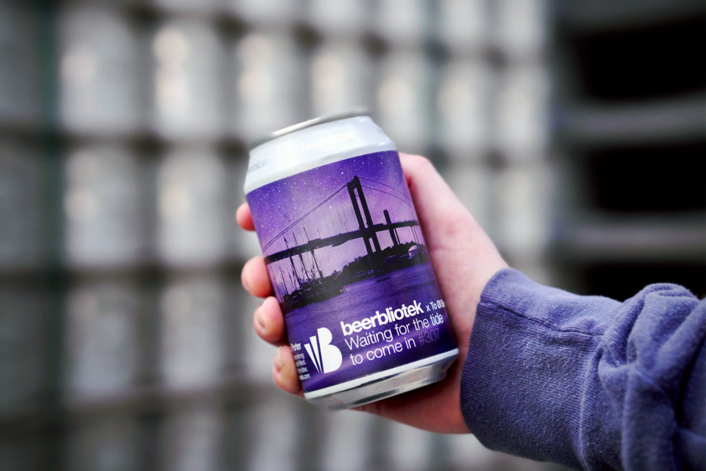 A photo of a can in hand of Waiting for the tide to come in, a Honey Baltic Porter, on packaging day, at Swedish Craft Brewery Beerbliotek. Brewed especially for Danish brewery To Øl and the To Øl Monthly Beer Club Box.