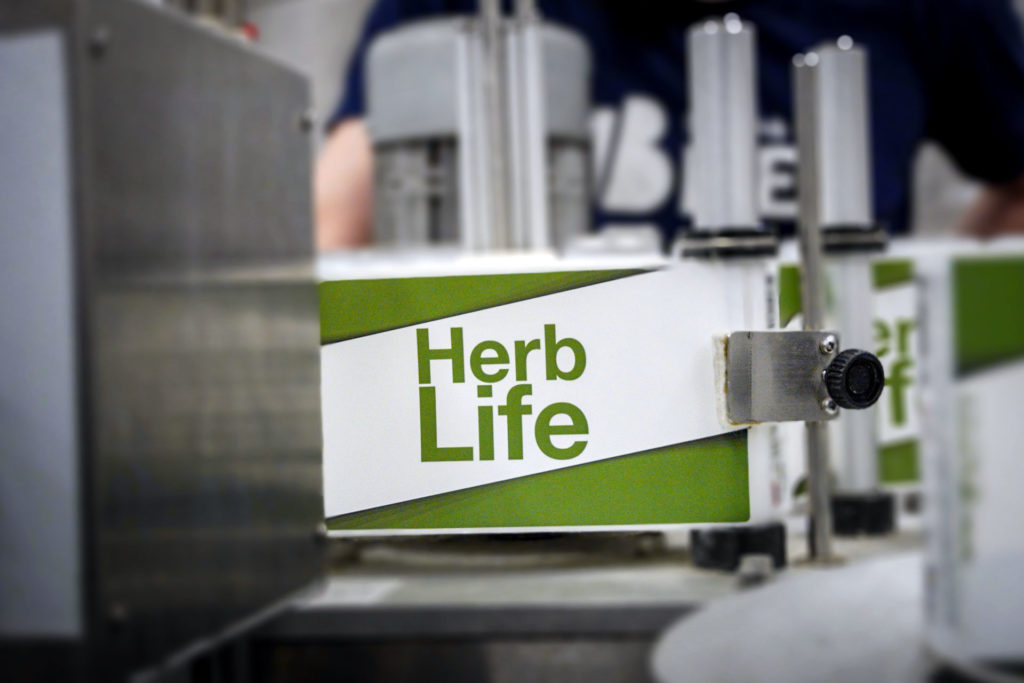 A photo of Herb Life, an India Pale Ale, being labelled on packaging day, at Swedish Craft Brewery Beerbliotek.