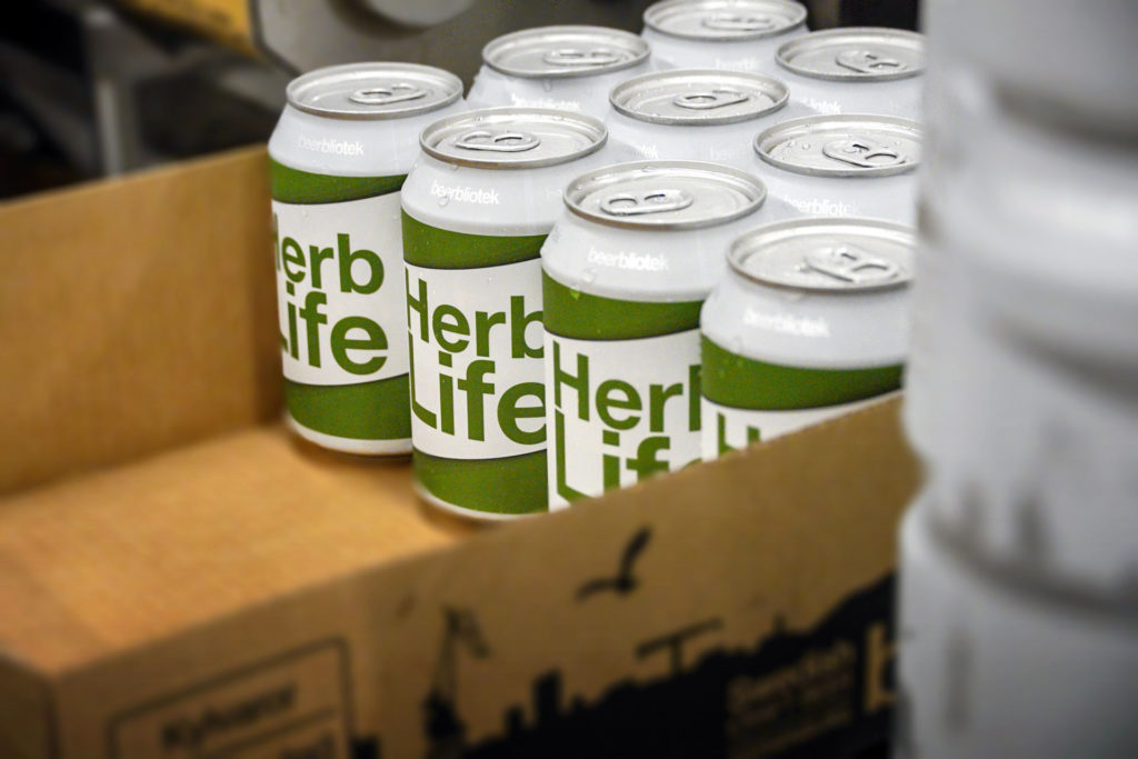 A photo of cans in a box of Herb Life, an India Pale Ale, on packaging day, at Swedish Craft Brewery Beerbliotek.