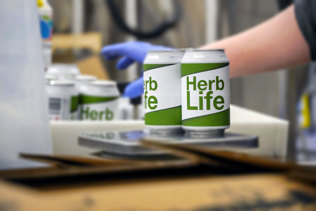 A photo of two cans of Herb Life, an India Pale Ale, on packaging day, at Swedish Craft Brewery Beerbliotek.