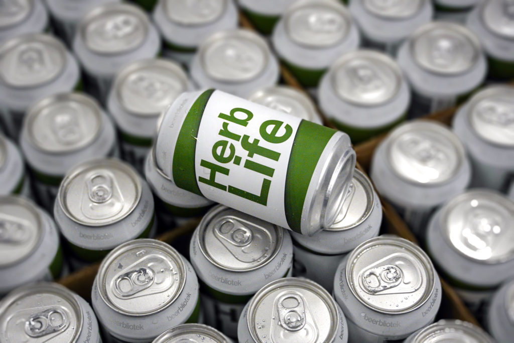 A photo of a can on top of boxes of cans of Herb Life, an India Pale Ale, at Swedish Craft Brewery Beerbliotek.