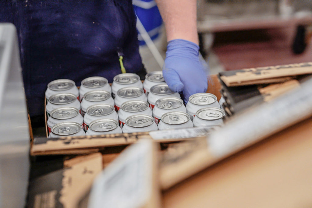 Cans of Amazing Maize, a Mexican Lager, being place into a box at Beerbliotek, a Craft Swedish brewery based in Gothenburg, Sweden.