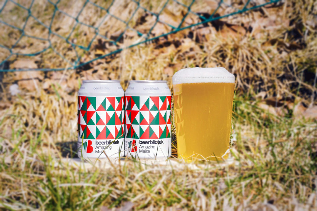 A tasting photo, two cans and one beer in a glass, of a Mexican Lager called Amazing Maize by Swedish Craft Beery Beerbliotek, from Majorna in Gothenburg, Sweden.